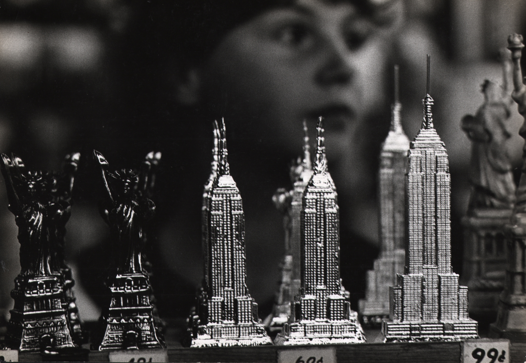 09. Jan Lukas, Souvenirs of New York, 1964. Miniatures of the Statue of Liberty, Chrysler Building, and Empire State Building for sale on a shelf. A child's face is out of focus behind them.