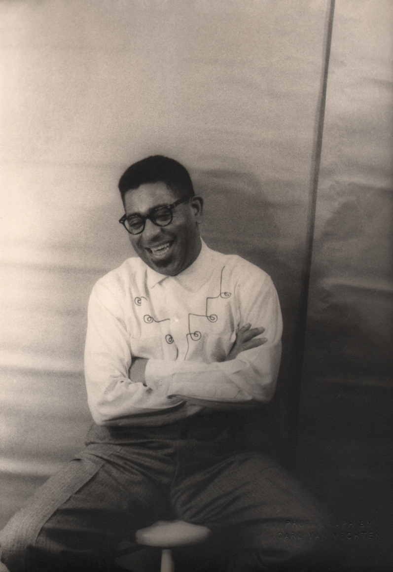 Carl Van Vechten, Dizzy Gillespie, 1955. Subject is seated with arms crossed, smiling with eyes cast down to the left.