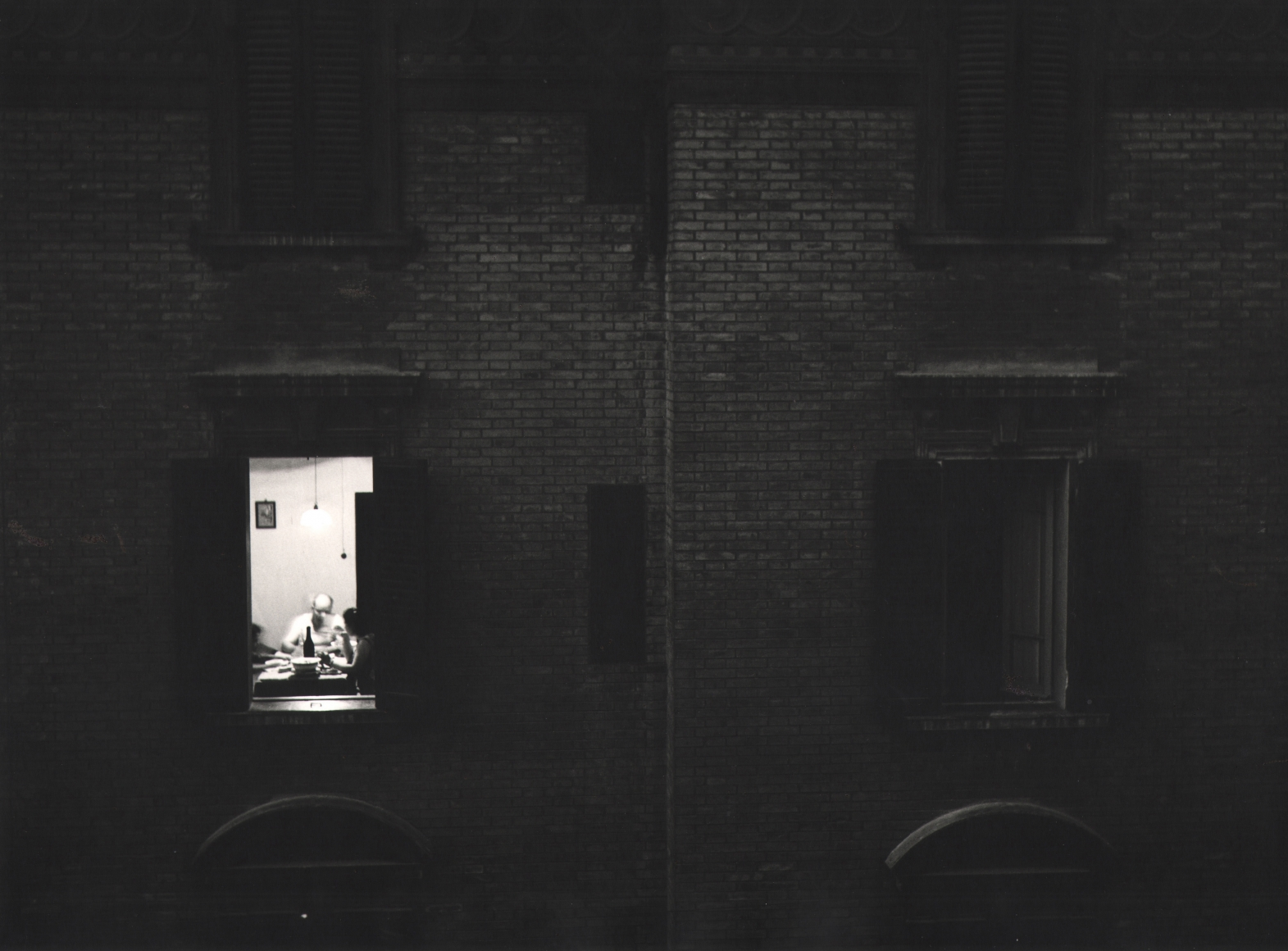 Nino Migliori, Summer evening from 'People of Emilia,' 1953. Exterior view of an apartment building. One window is lit and a family is seated at the dinner table.