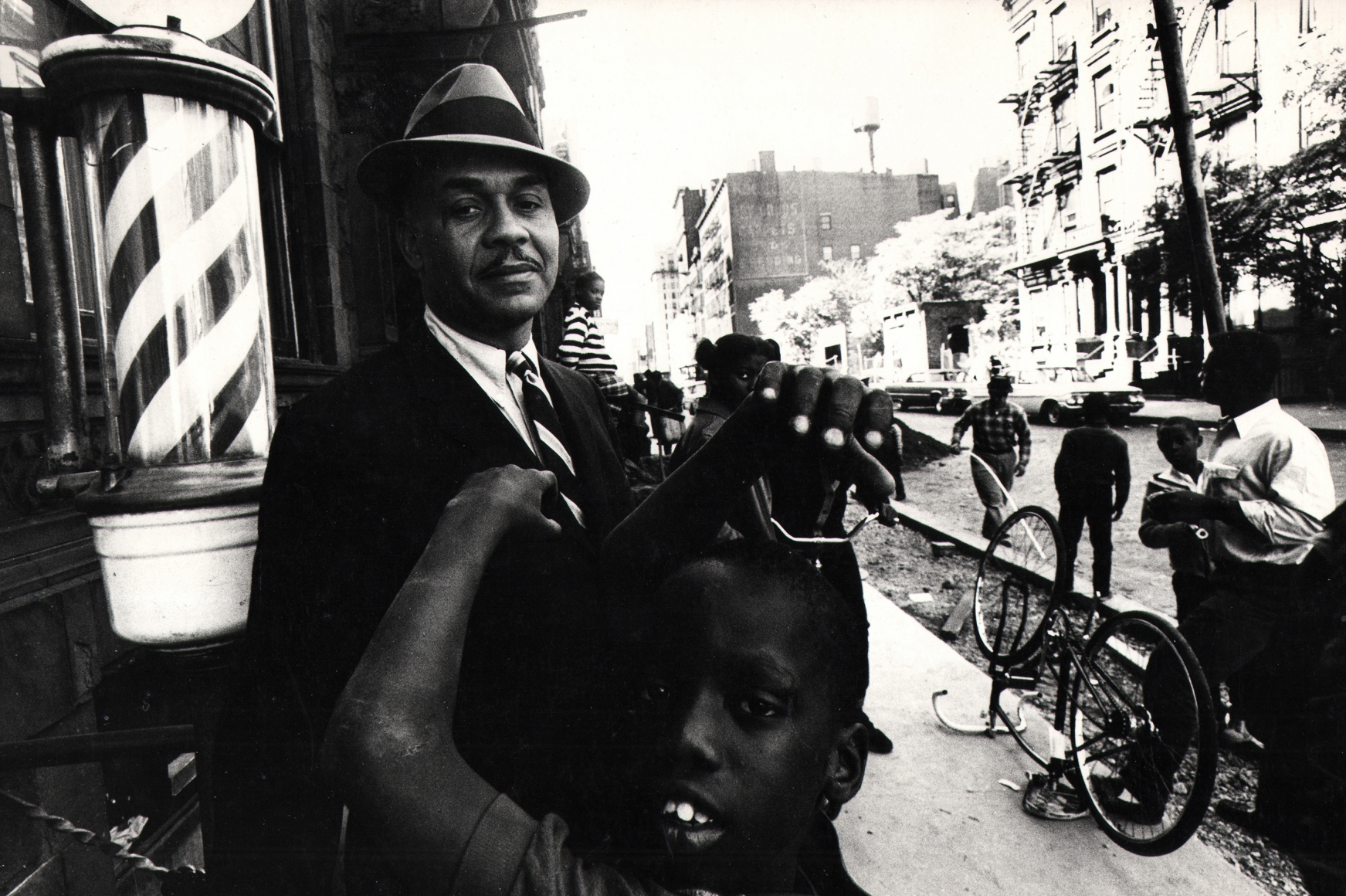 David Attie, Ralph Ellison in Harlem, 1966. Subject poses on the street beside a barber shop, looking into the camera as various figures move around him.