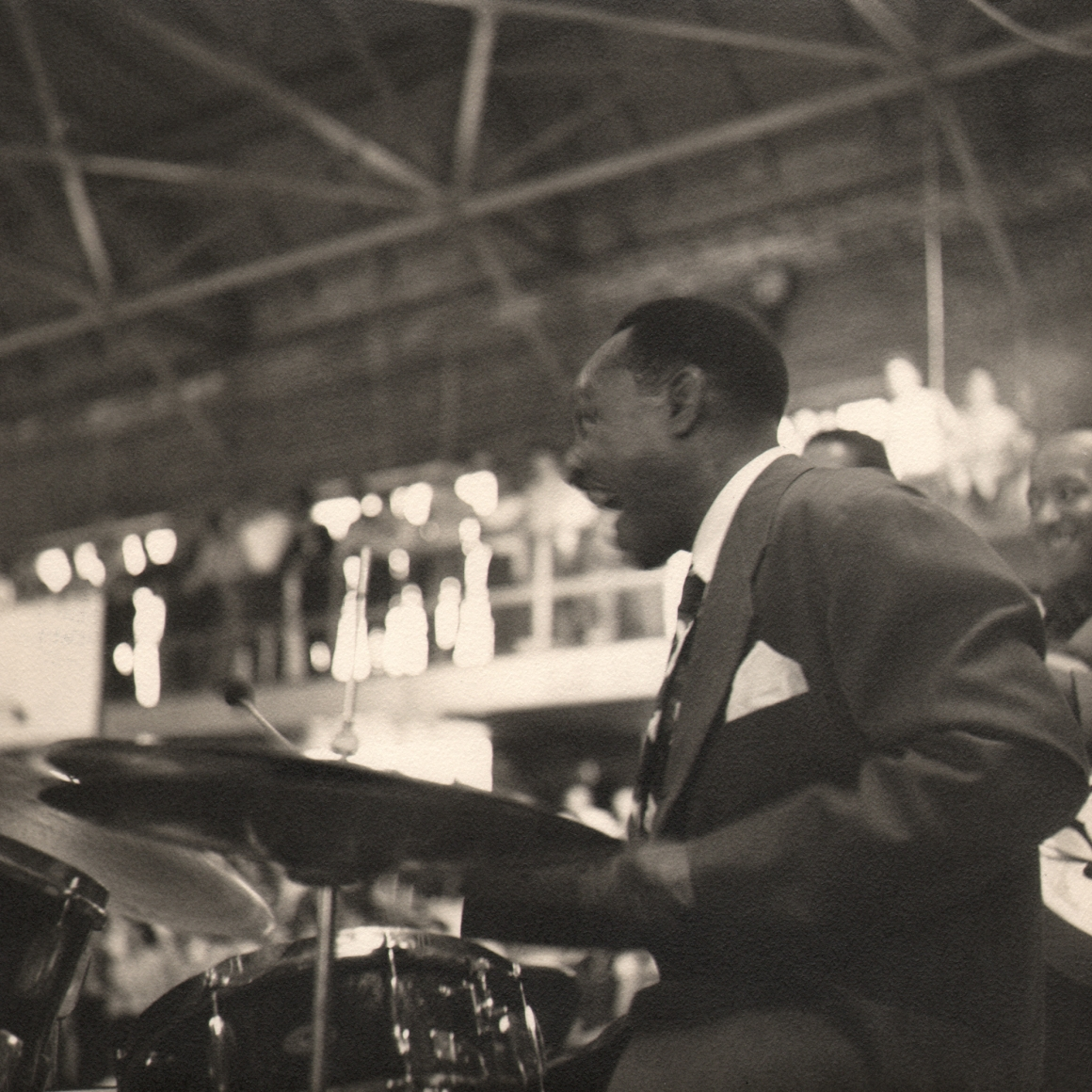 Bob Willoughby, Lionel Hampton, 1956. Subject is seated at a drumset on the right side of the frame, facing left and smiling.