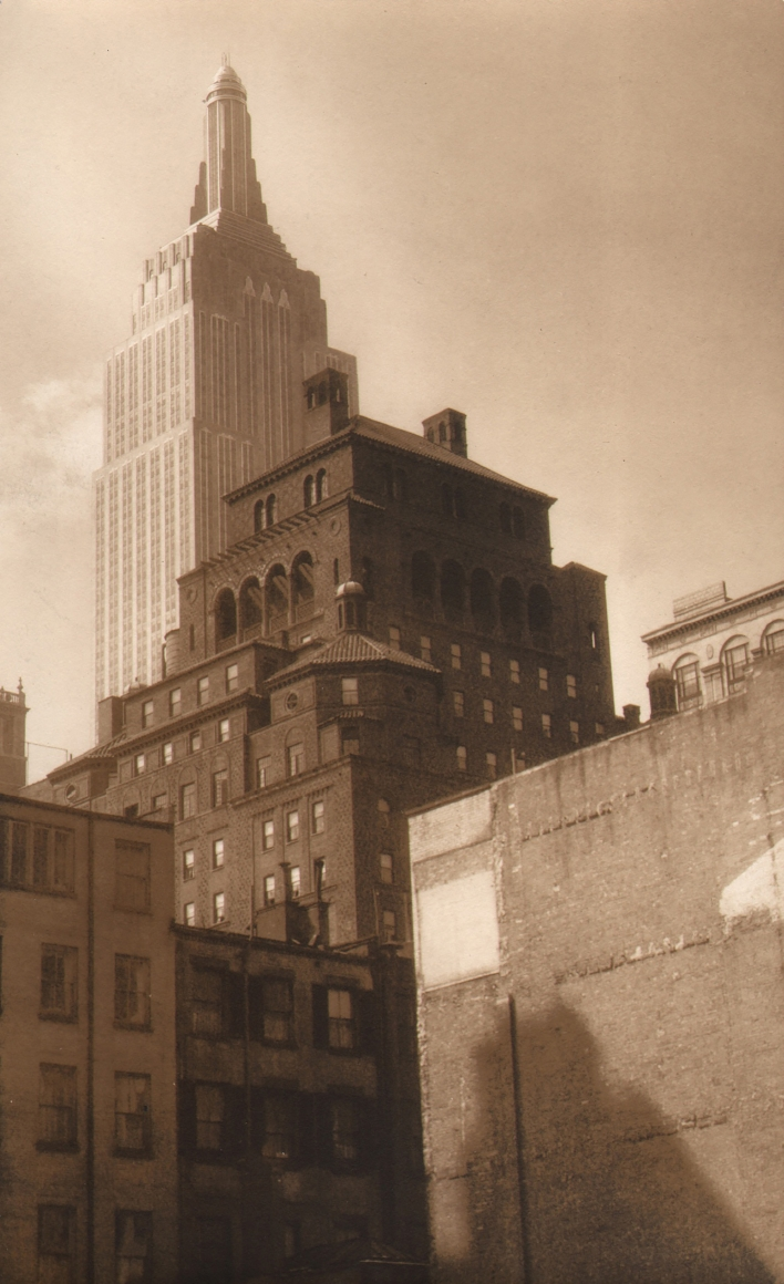 Paul J. Woolf, Empire State from Park Avenue, c. 1933. Shorter buildings converge in the foreground with the Empire State Building in the upper left of the frame in the background.