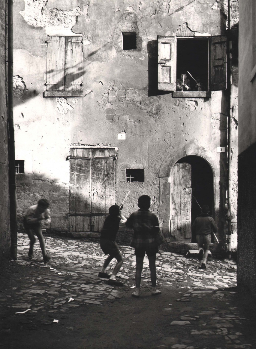 Nino Migliori, The Street Kids, 1955. Six boys play with peashooters in an alley. Four are on the street, two are leaning out a second story window.