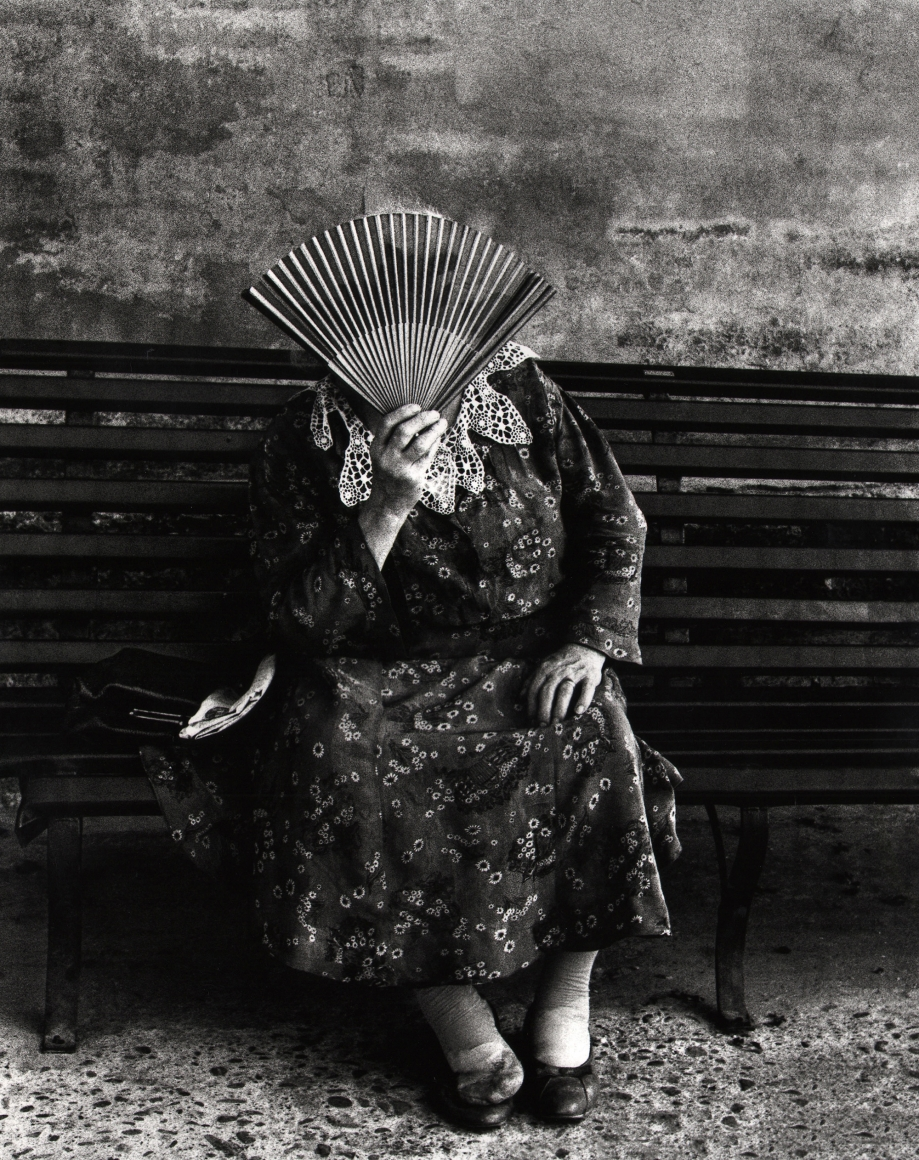 Nino Migliori, People of the South, 1956. A woman seated on a bench, holding a paper fan in front of her face.