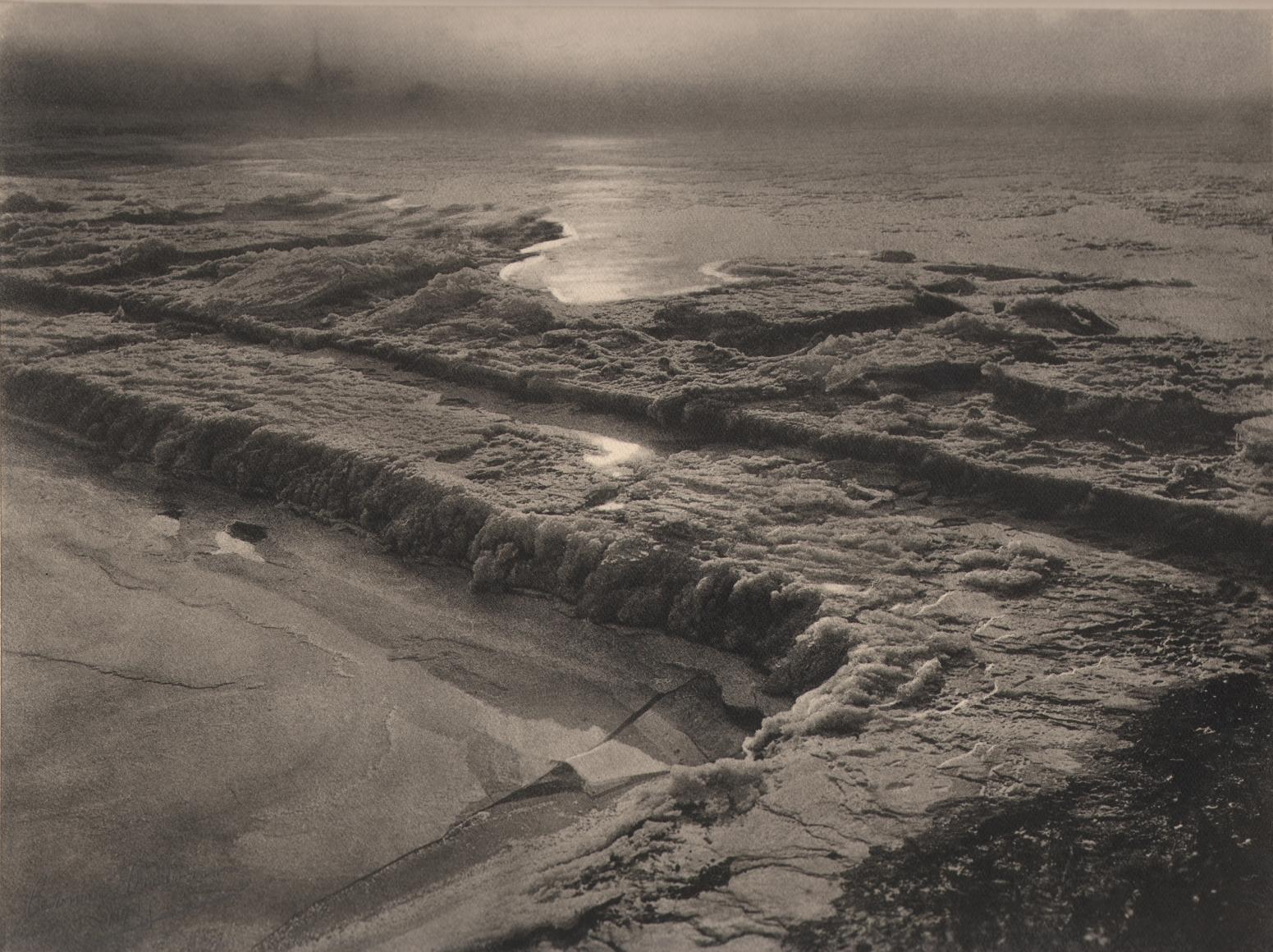 11. Léonard Misonne, Le barrage gelè, c. 1935. Frozen body of water in early morning, hazy light. Sepia-toned print.