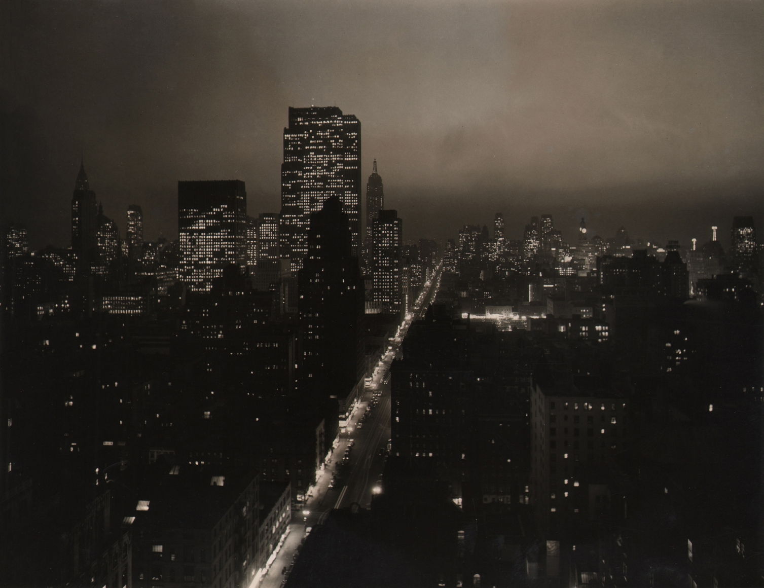 Paul J. Woolf, Sixth Avenue Looking South, c. 1935. Night time cityscape with an illuminated Sixth Avenue running diagonally up and right in the center of the frame.