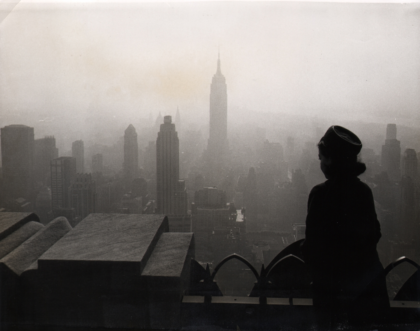 17. UPI Photo, Smog-Bound City, 1965. A silhouetted woman stands on a balcony, looking out towards a foggy skyline that includes the Empire State Building at the center.