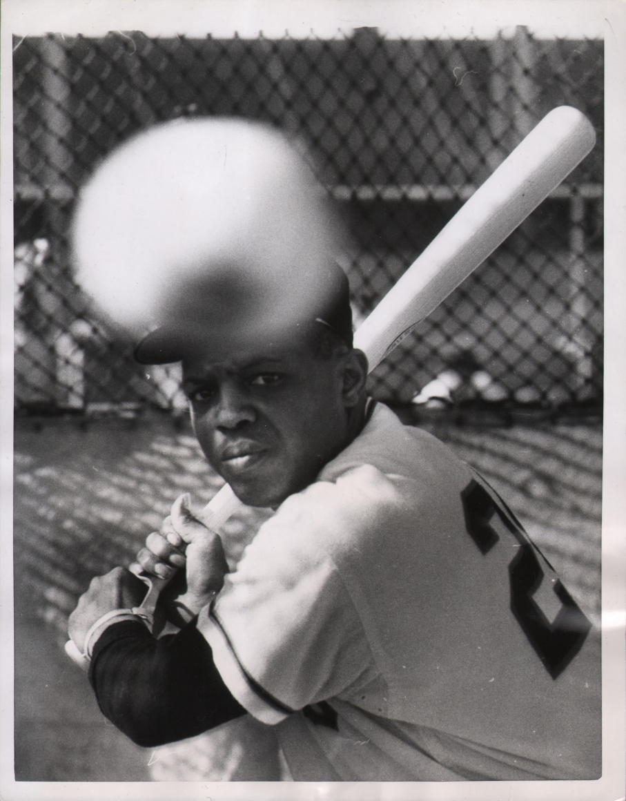 United Press Photo, A Pitcher of Willie, 1958. Subject holds his baseball bat at the ready as a baseball (out of focus in the foreground) flies toward him.