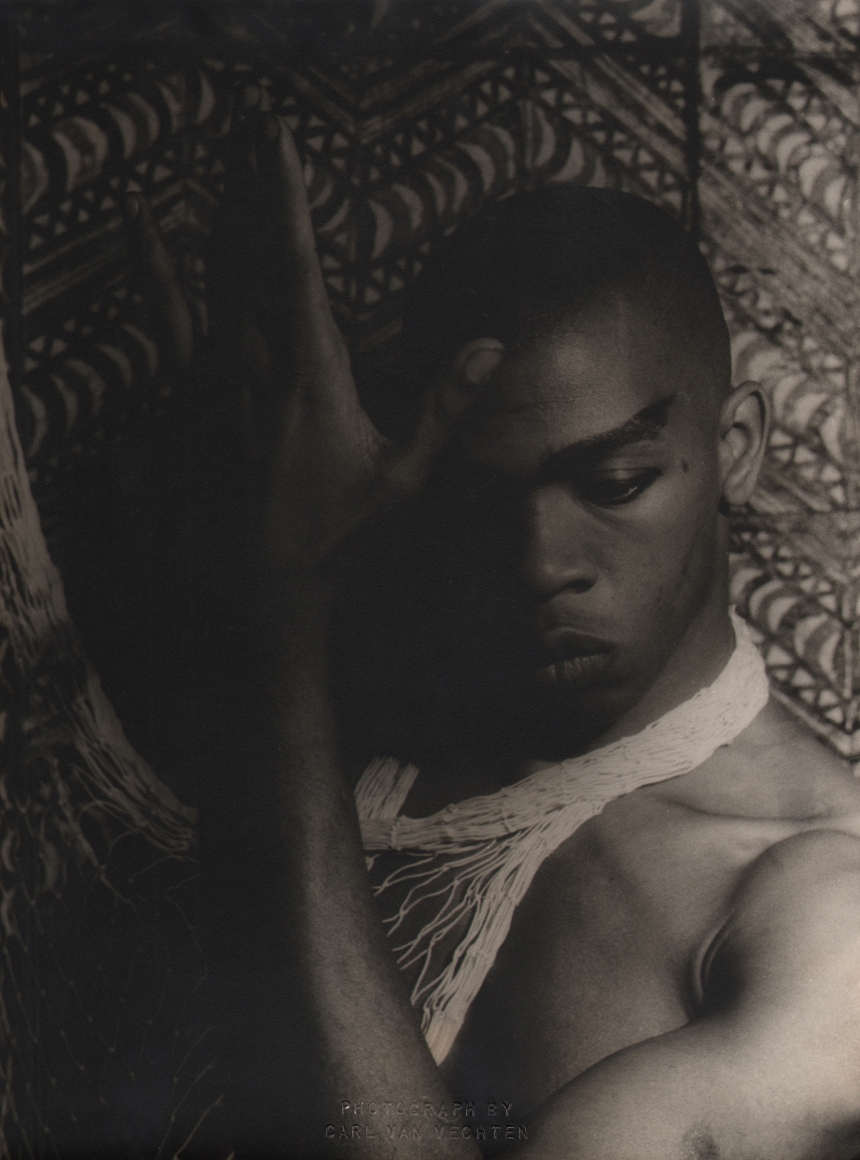 Carl Van Vechten, Geoffrey Holder, 1954. Subject poses shirtless with one hand raised by his face, eyes cast downward.