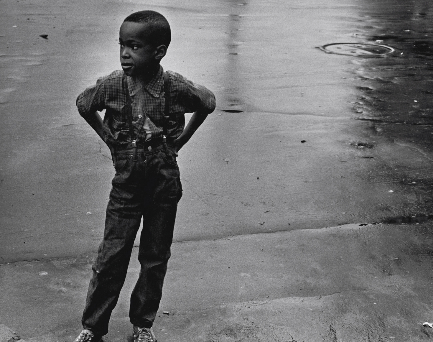 29. Beuford Smith, Boy in Street, Brooklyn, 1969. A young boy in suspenders stand with hands on hips on wet pavement, looking to the left of the frame.