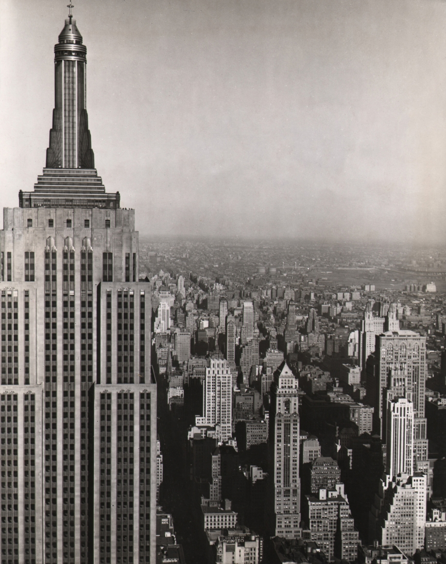 21. Anonymous, Heading Straight for the Empire State Building, 1939. Straight- on view of the top half of the Empire State Building, about level with the highest observation deck. The building occupies the left third of the frame, with the city skyline and horizon on the right.