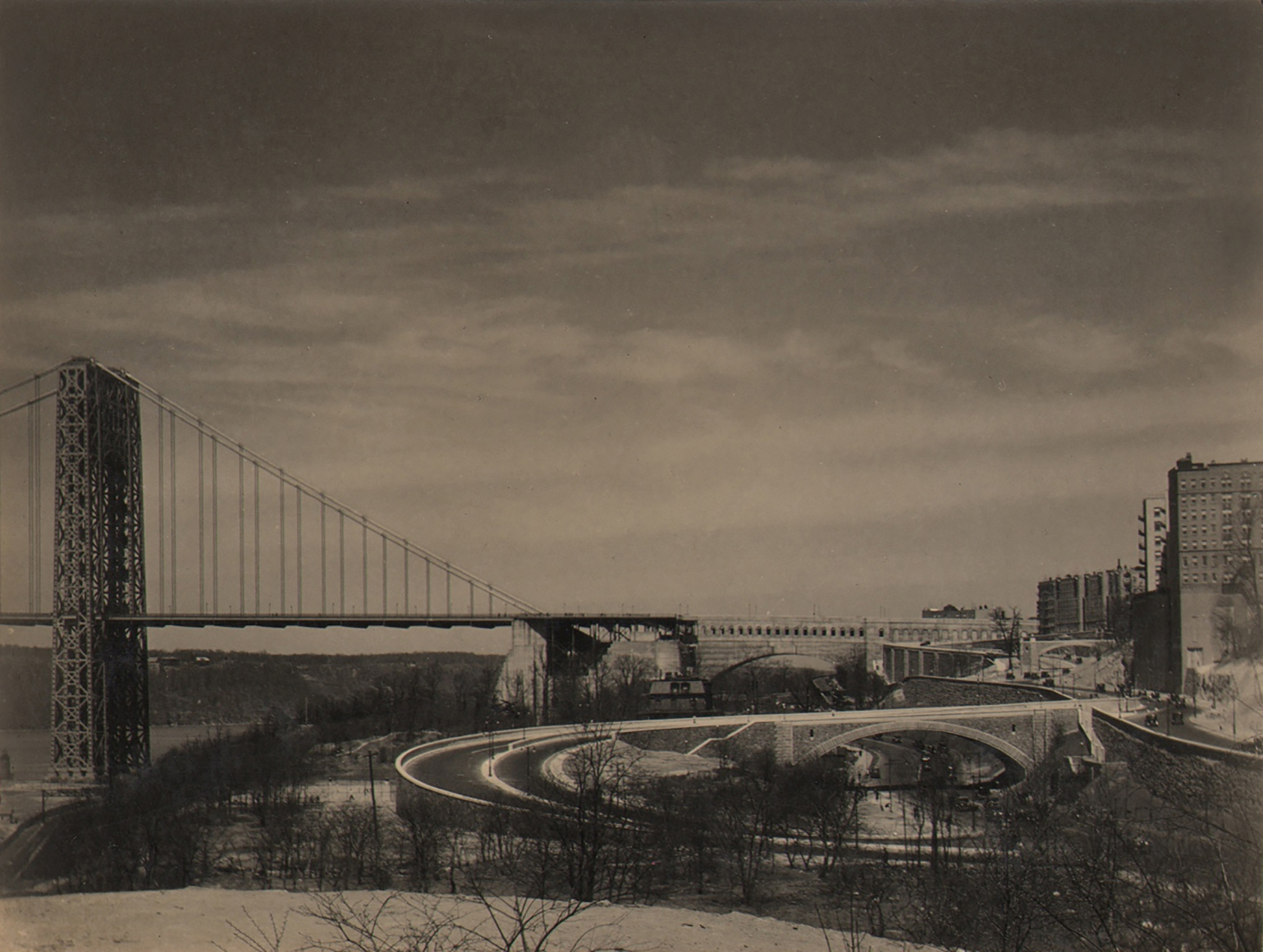 Paul J. Woolf, George Washington Bridge, c. 1933. Cityscape with bridge on center left of the frame. Cloudy sky above. A few buildings are visible on the far right.