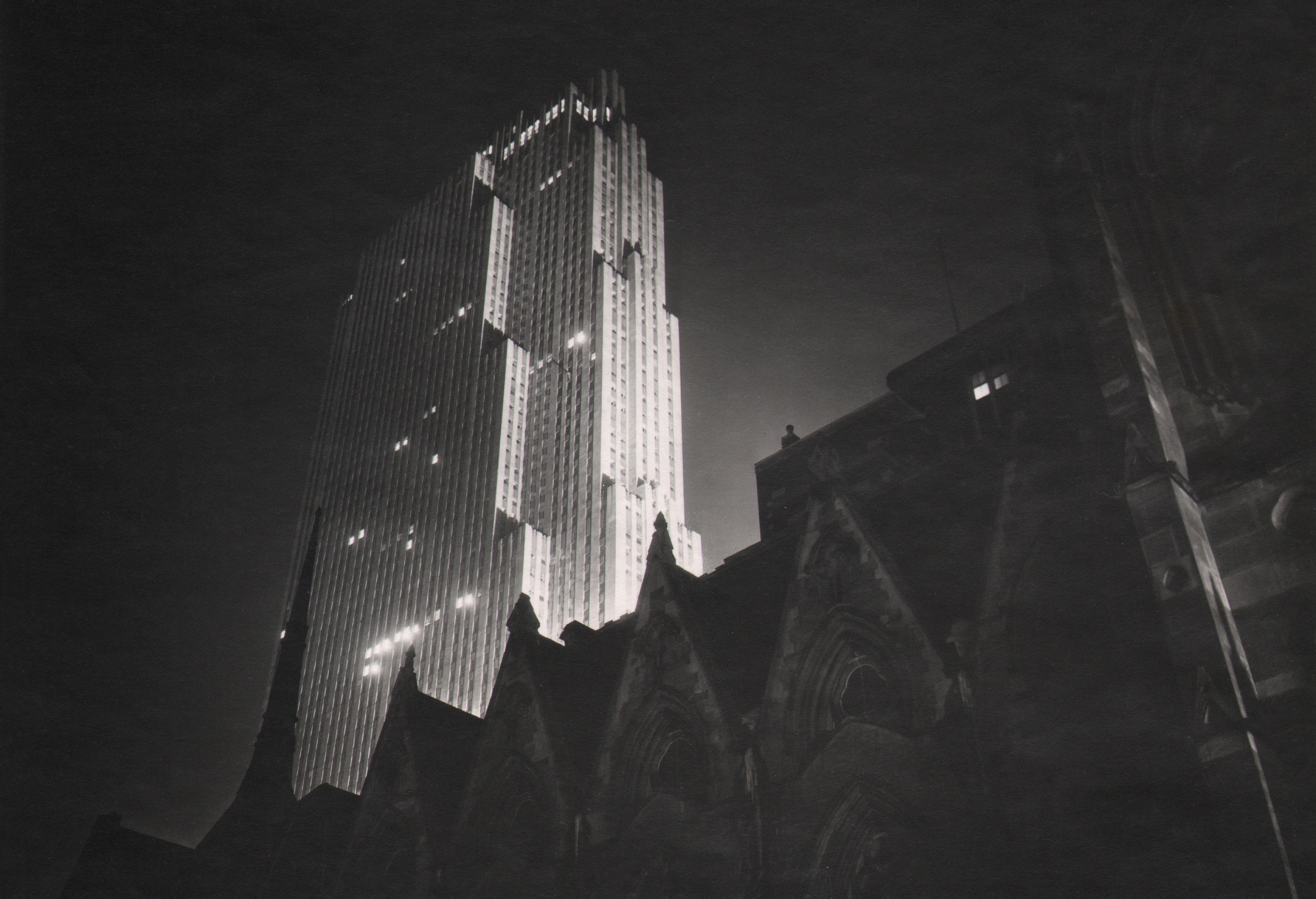 Paul J. Woolf, RCA Building at Night, c. 1936. Silhouetted cathedral in the foreground against the tall RCA Building rising up on the center left of the frame.