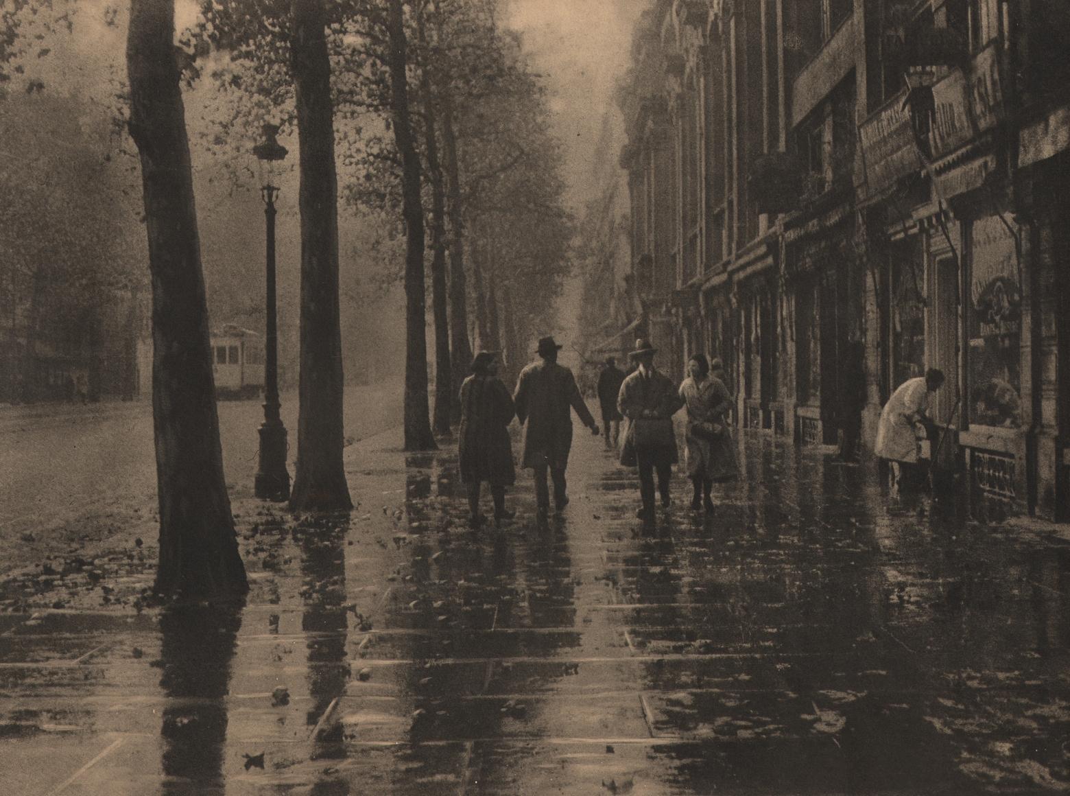 02. Léonard Misonne, Untitled, c. 1932. Pedestrians walk a tree-lined, wet sidewalk. Sepia-toned print.