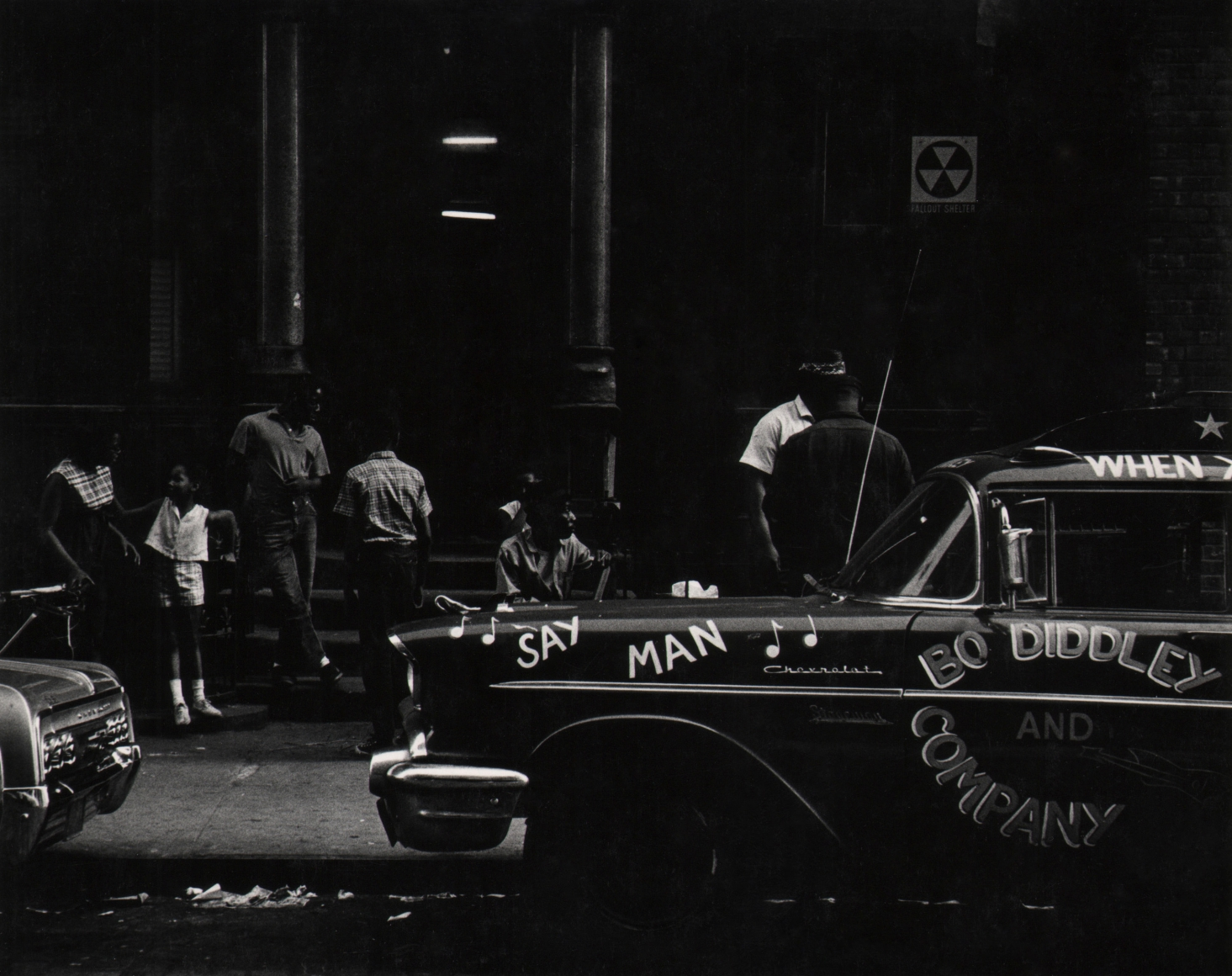 """30. Beuford Smith, Say Man, Harlem, 1969. A car parked on the street that reads """"Say Man"""" and """"Bo Diddley and Company"""". Figures gathered on the sidewalk behind."""