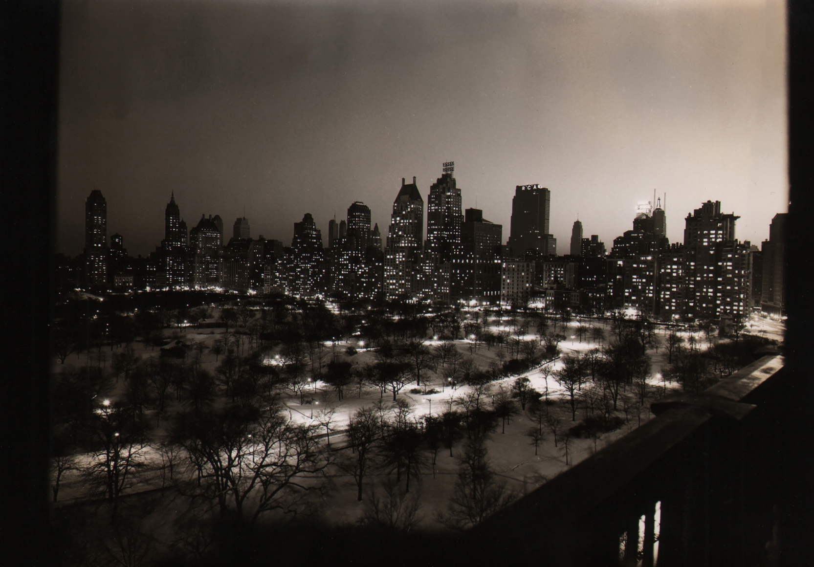 Paul J. Woolf, Central Park & 59th Street, c. 1936. Night time cityscape with Central Park in the foreground and tall buildings in the background.