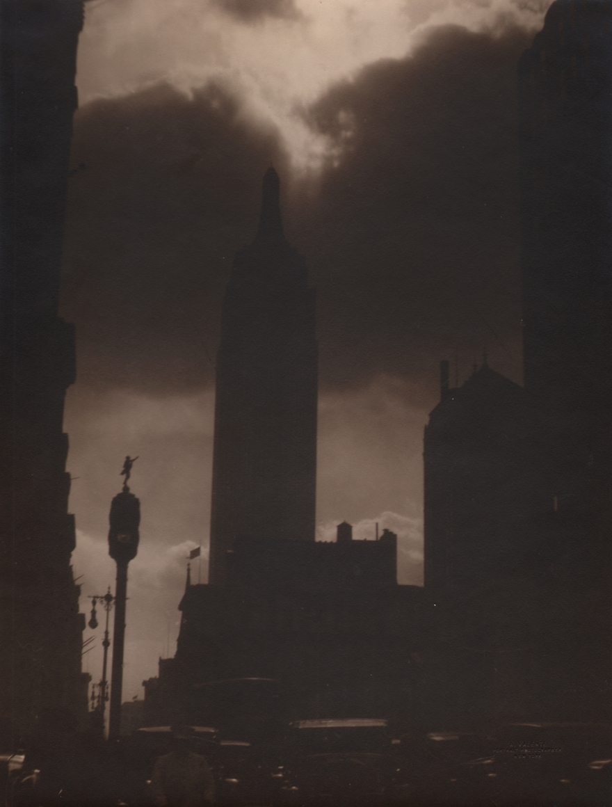 31. Alfredo Valente, Empire State Building, c. 1933. Sepia tone street view of silhouetted Empire State Building against a cloudy sky.