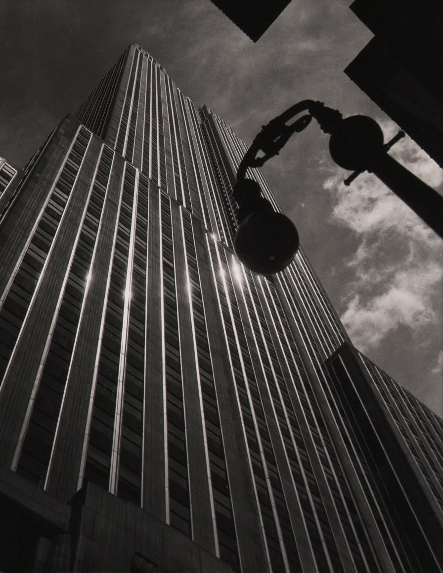 12. John C. Hatlem, Empire State Building, c. 1935. Upward-looking street-level view from below the reflective Empire State Building. A streetlight is silhouetted against a clouds and sky on the right of the frame.