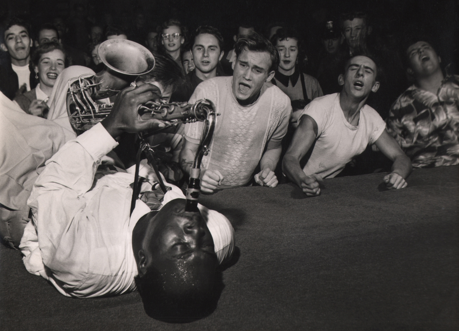 Bob Willoughby, Big Jay McNeely, 1951. Subject lays on stage mid-performance, playing the saxophone while emotional fans look on.