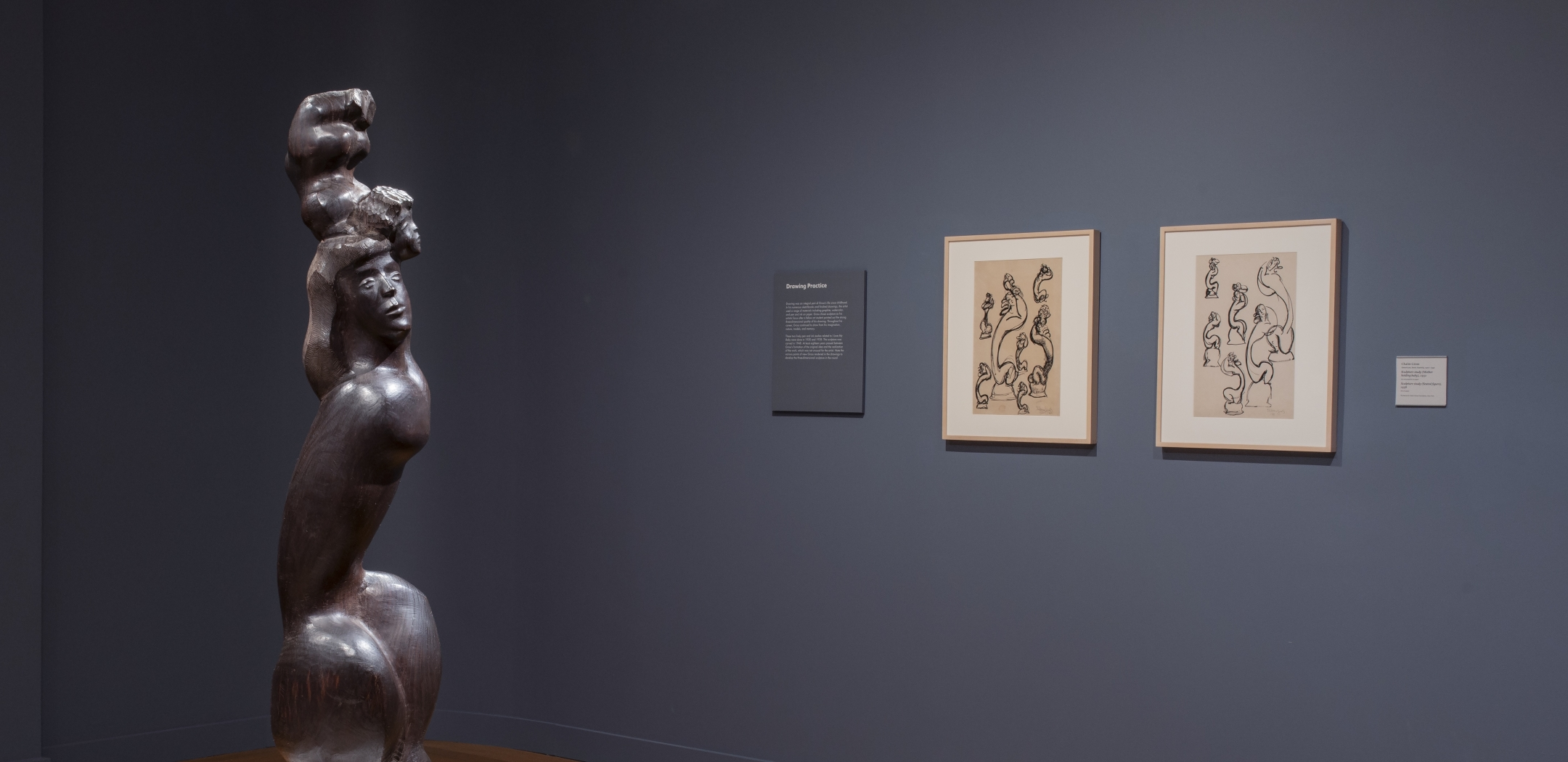 Photo of a wooden sculpture, I LOVE MY BABY, 1948, depicting a woman with long hair, crouched so that her legs are drawn close to her tall torso. She is supporting the figure of a baby, whose head touches hers but whose body is raised above its head. To the right of the sculpture are two framed ink sculpture studies for the same sculpture. The walls are faded navy.