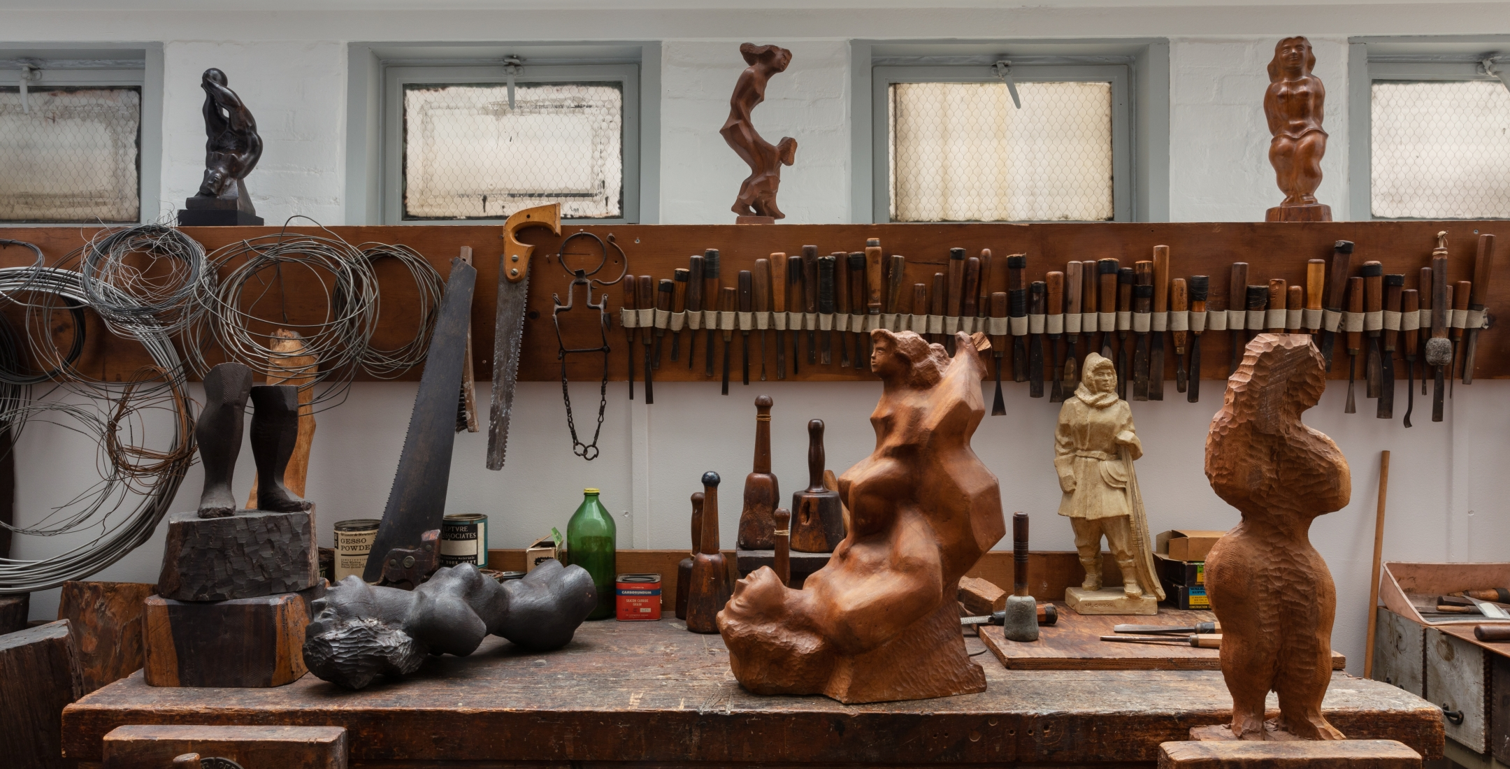 Photo of Chaim Gross' workbench. In the background there is a row of sculpting tools, wires, and small sculptures. In the foreground, on the workbench, there are a few larger wooden sculptures of the human figure.