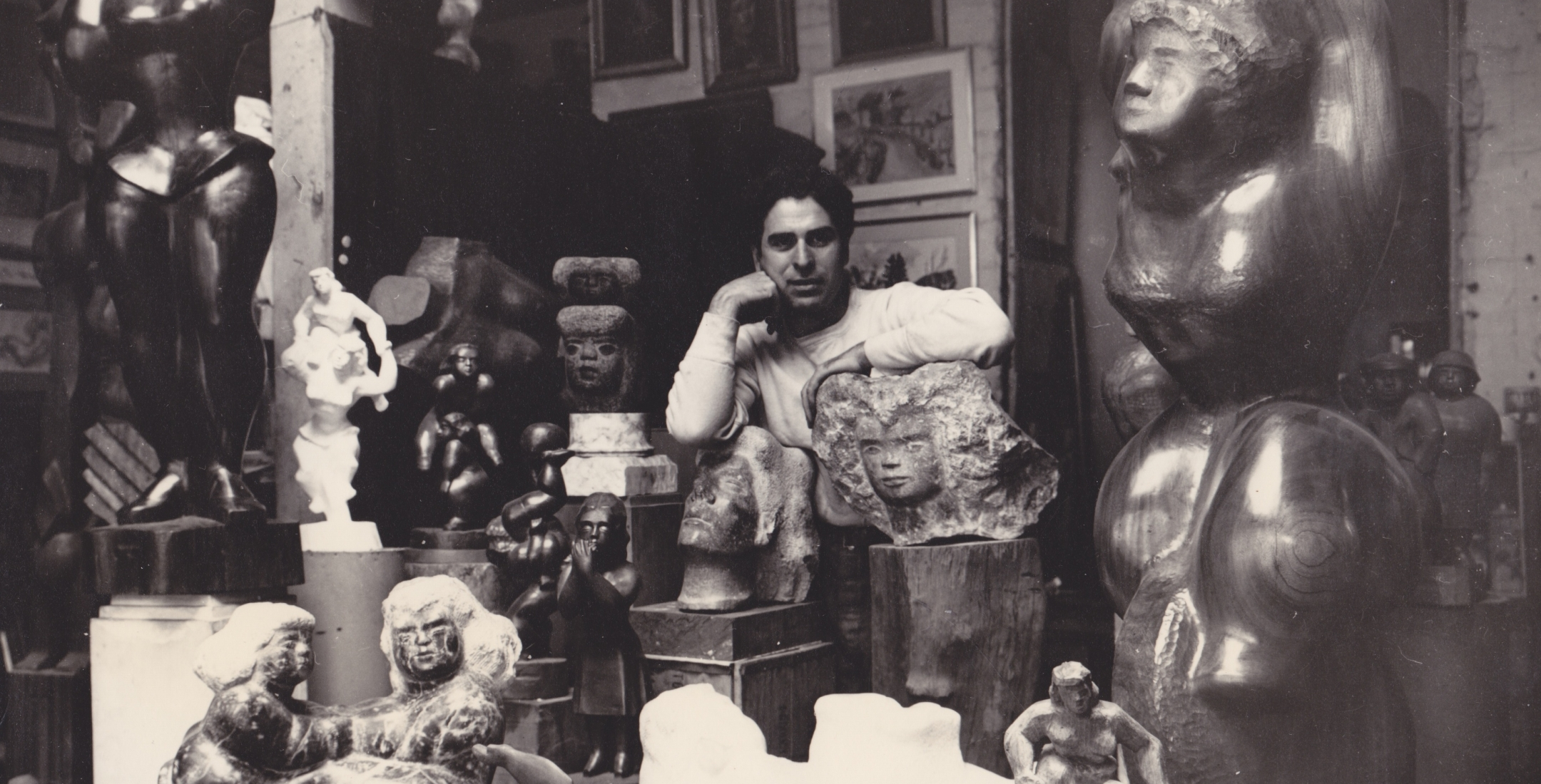 Black and white photo of a young Chaim Gross looking at the camera while surrounded by sculptures of various sizes and mediums.