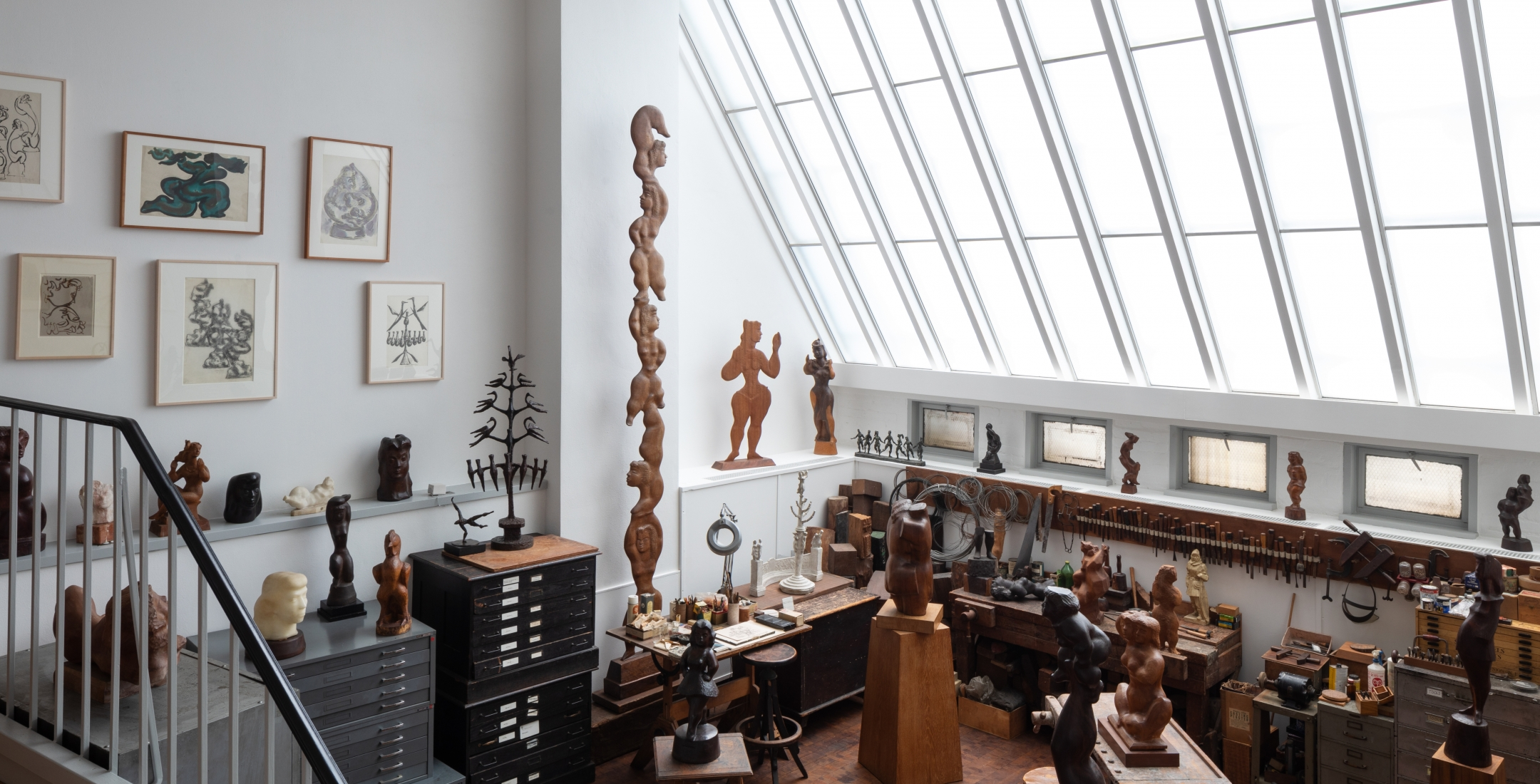 Photo of the studio at 526 LaGuardia Place. There is a skylight along the right half of the space that floods the sculptures, tools, and materials with light. There are drawings on the wall and many sculptures of human figures in wood.