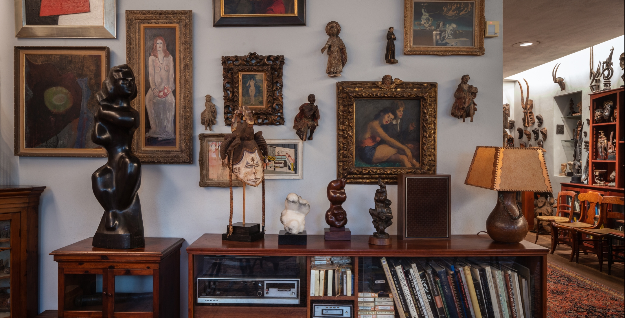 On a wooden table are various small sculptures and a brown lamp. On the grey wall are small mounted sculptures and various paintings of different sizes. The photo reveals a row of chairs and more mounted sculptures in the distance, around the corner.