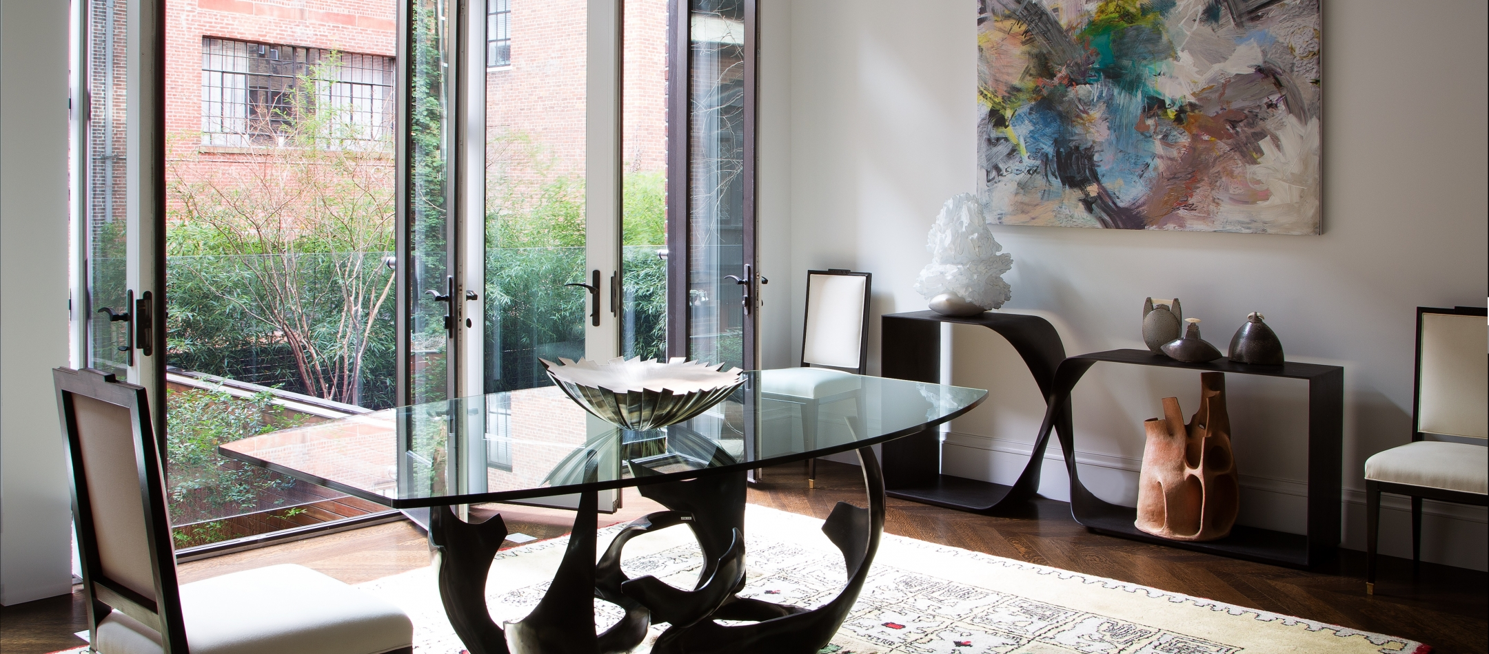 Three of a set of six dining chairs made by Andre Mercier circa 1940; a glass topped, patinated bronze dining table by Fred Brouard; a table top sculpture by English silversmith Kevin Grey; and one of a pair of Maison Leleu carpets from 1957.