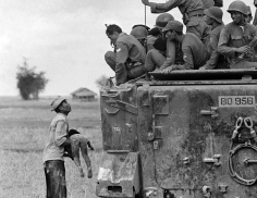 Horst Faas- A Distraught Father Holds the Body of his Child as South Vietnamese Rangers Look Down from their Armored Vehicle