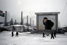 Hiroji Kubota, At the Kim Chaek Ironworks; the billboard shows Kim Il-sung peering into a furnace, Chongjin, North Korea, 1986, dye-transfer print, 20 x 24 inches/50.8 x 61 cm © Hiroji Kubota/Magnum Photos