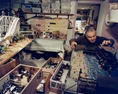 Man in his basement with models of North End businesses, including his barbershop, Boston, MA, 2003