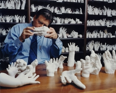 Surgeon with molds of hands he has repaired, Brookline, MA, 2002