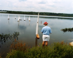 Man at radio-controlled sailboat regatta, Gilford, NH, 2003