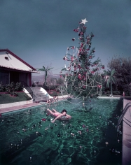 Slim Aarons, Christmas Swim, 1954: Rita Aarons swimming in a pool festooned with floating baubles and a decorated Christmas tree, Hollywood, California