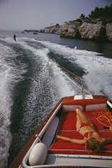 Slim Aarons, Leisure in Antibes, 1969: A woman sunbathes on a motorboat as it tows a waterskier in the bay off the Eden-Roc