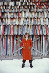 Slim Aarons, Princess Ruspoli, 1979: Princess Lucy Ruspoli stands in front of a colorful wall of old skis in Lech am Arlberg, Austria