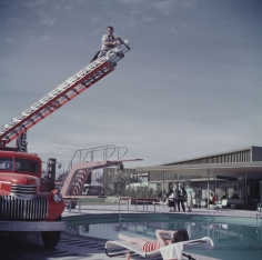 Slim Aarons, To Any Lengths, 1954: Slim Aarons photographing Mara Lane from the top of an extending ladder by the swimming pool at Sands Hotel, Las Vegas