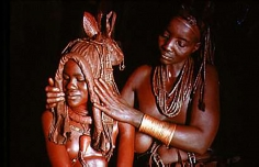 Carol Beckwith and Angela Fisher, Himba bride is prepared for marriage by her mother wearing an ekori headdress, Namibia