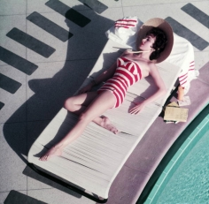 Slim Aarons, Mara Lane at The Sands, 1954: Austrian actress Mara Lane lounging by the pool in a red and white striped bathing costume, Las Vegas