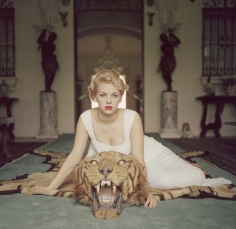 Slim Aarons, Beauty And The Beast, 1959: Lady Daphne Cameron (Mrs. George Cameron) on a tiger skin rug in the trophy room at socialite Laddie Sanford's home, Palm Beach