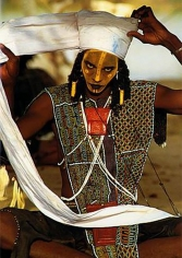 Carol Beckwith and Angela Fisher, Wodaabe man wraps a twelve-foot-long turban in preparation for the Yaake charm dance, Niger