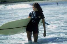 Slim Aarons, Minnie Cushing, 1965: American society girl Minnie Cushing carries her surfboard under her arm