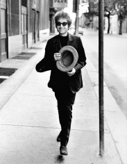 Daniel Kramer, Bob Dylan walking with top hat, Philadelphia, PA, 1964