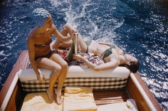 Slim Aarons, Carla Vuccino and Marina Rava sit on the rear of a boat, on the waters off the coast of the island of Capri, Italy, 1958