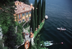 Slim Aarons, Giacomo and Stefania Montegazza welcome guests arriving by boat at their villa, La Casinella, on Lake Como, 1983