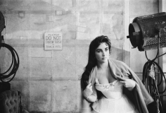 """Bob Willoughby, Elizabeth Taylor throws a dressing gown over her costume on the MGM set of """"Raintree County"""", 1956"""