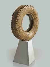 A large tire, scaled up and hand carved out of wood.