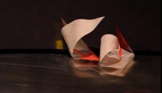 A photograph of a video still from the HD video included in this artwork. In the image there are 2 pieces of paper, curling over themselves, with dots of red paint at the corner.