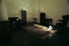 Hale Tenger, Shroud, 1996, Found furniture, carpet, fan, spotlight, toddler shoes and photographs, and shroud